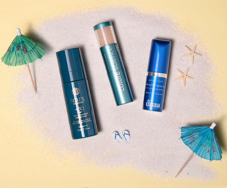Sun care products with sand and umbrella-1 | Dermstore Blog